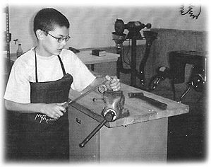 Jared, 11, in the family's home based machine shop, McArthur Machine Tool, where Jared can use simple tools, like the vise he is using.